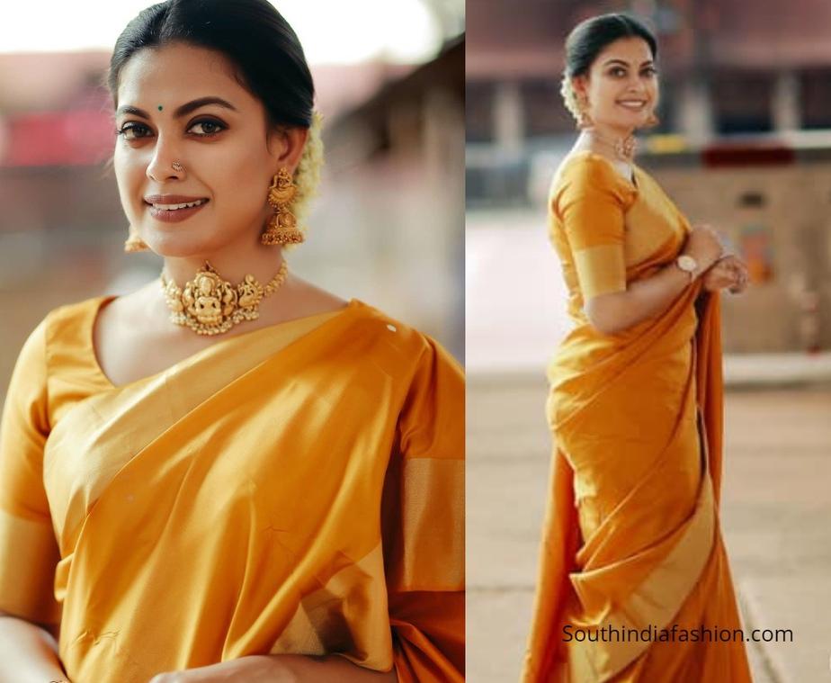 Actress Anusree in a golden orange pattu saree in guruvayur
