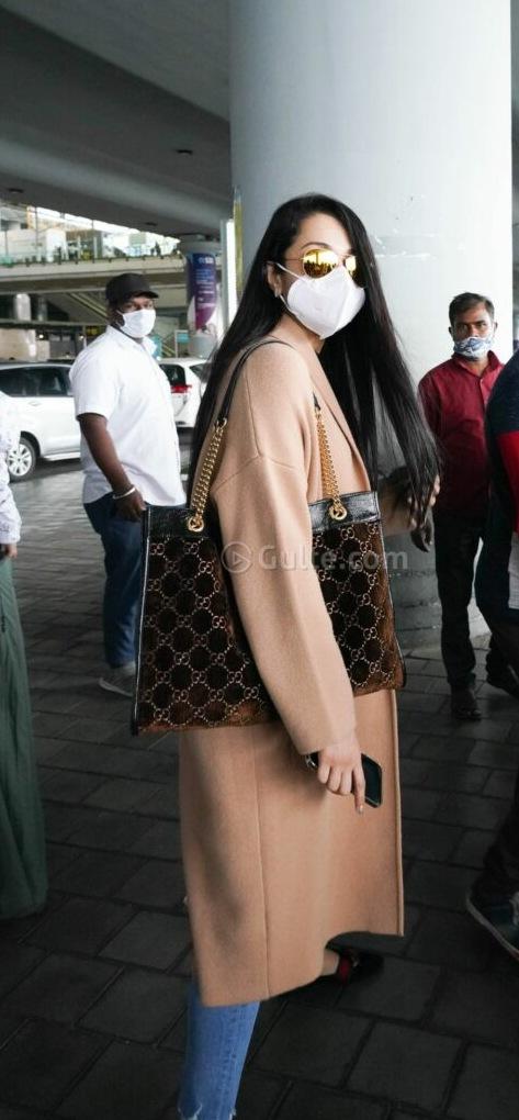 Trisha in long coat and denim at airport