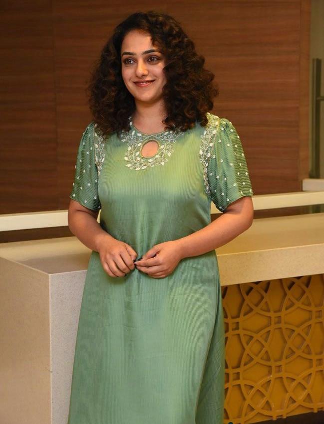 nithya menen in a green asymmetrical kurta at movie interview