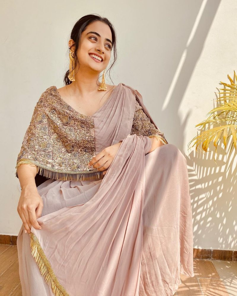 namitha pramod in a beige saree gown with brown cape