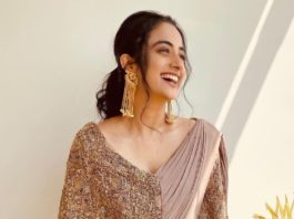 namitha pramod in a beige saree gown with tasseled cape