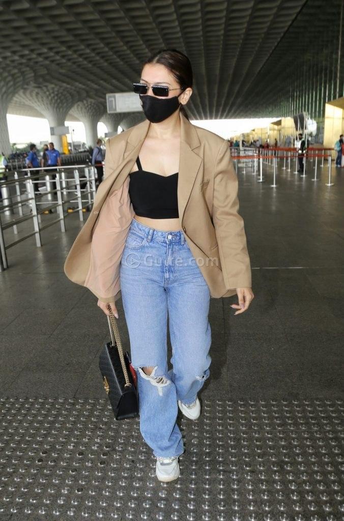 Hansika Motwani in coat -baggy jeans at airport