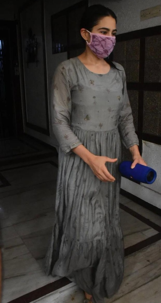 When it comes to talking about passion for traditional wear, Sara Ali Khan strikes our mind first. She loves wearing Indian in her day-to-day life. The paps can't stop drooling over this royal beauty who never fails to amaze us even in her ethnic outfits. Sara Ali Khan was spotted outside her gym wearing a long grey Anarkali-shaped dress. The dress featured full sleeves and light golden embroidery running all over. Further, it had pleats starting from the waist area to the bottom end of the outfit. As she was clicked outside her gym, she went for a no-makeup look as most of her face was shielded with an embroidered pink mask. also, she skipped on wearing any accessories to keep it simple and basic. Due to her long dress, her footwear was not really visible, but we could spot regular golden slip-on. Lastly, her hair was tied in a cute ponytail that accentuated her look.