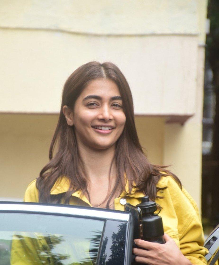 Pooja Hegde in casual yellow denim jacket and black track pants at Bandra-1