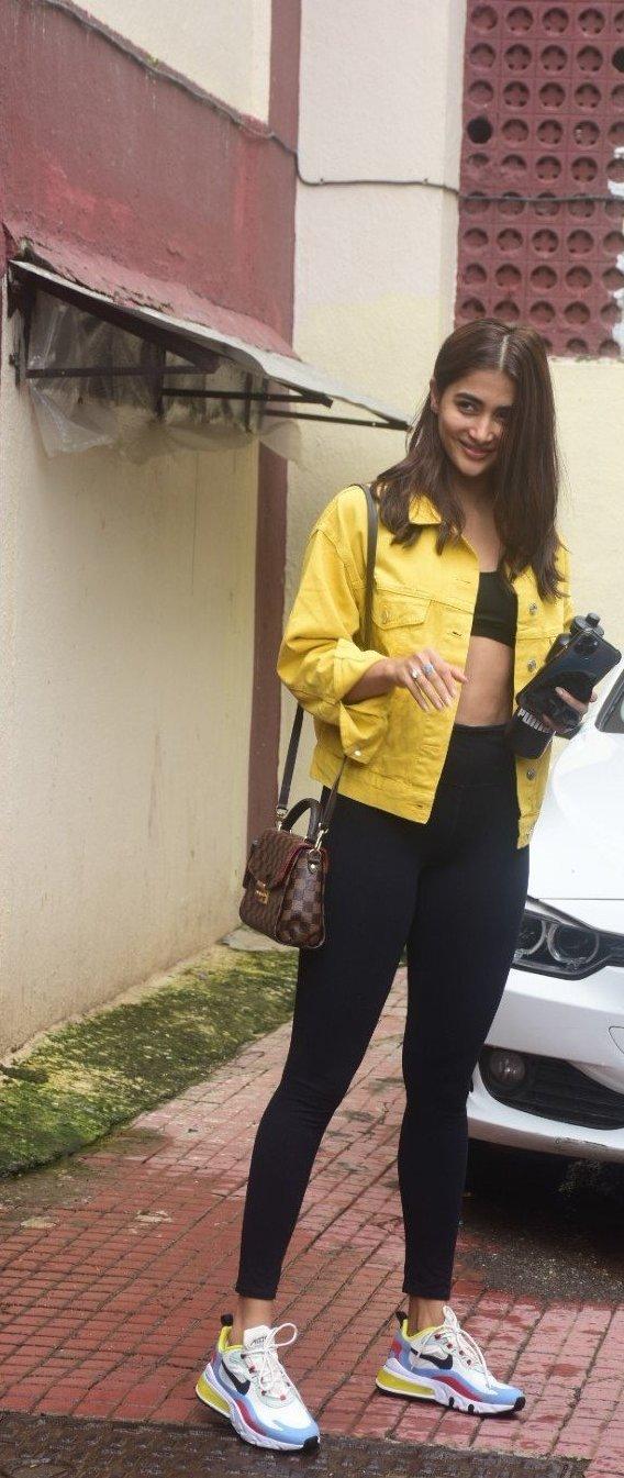 Pooja Hegde in casual yellow denim jacket and black track pants at Bandra-2