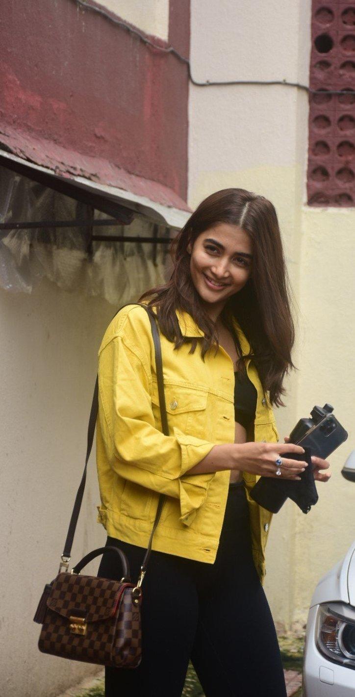 Pooja Hegde in casual yellow denim jacket and black track pants at Bandra-3