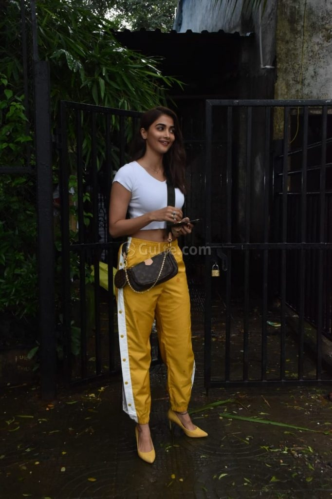 Pooja Hegde in side slit yellow pants and white crop top at Rohan Shresta's office-1