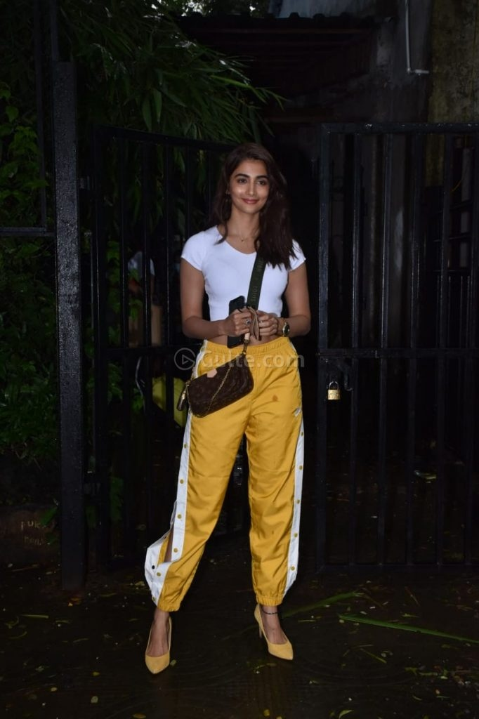 Pooja Hegde in side slit yellow pants and white crop top at Rohan Shresta's office-2