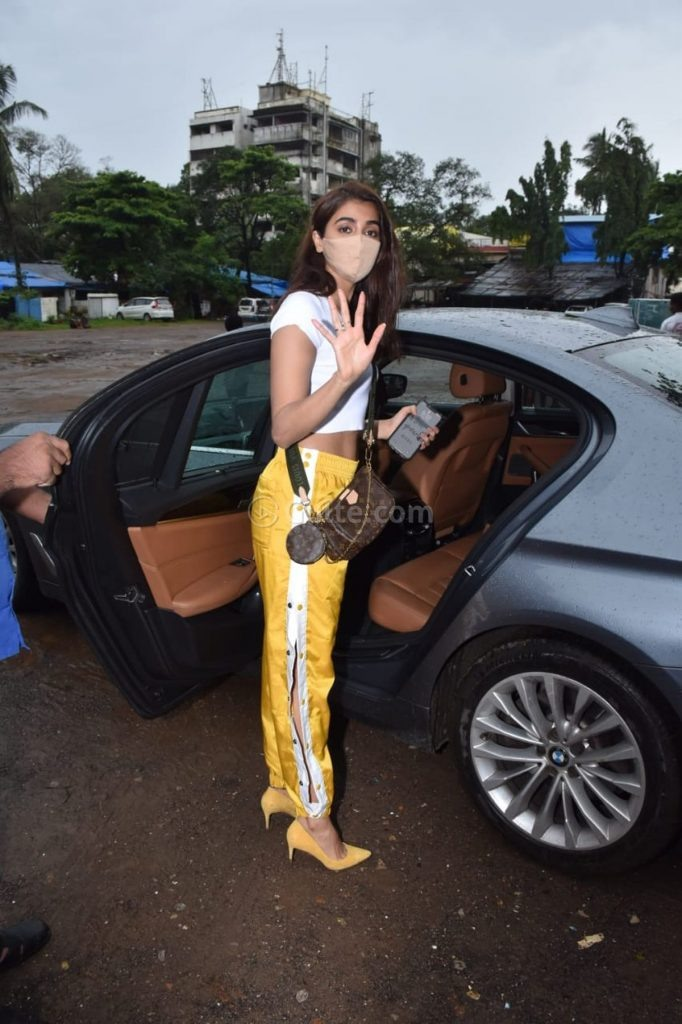 Pooja Hegde in side slit yellow pants and white crop top at Rohan Shresta's office-4