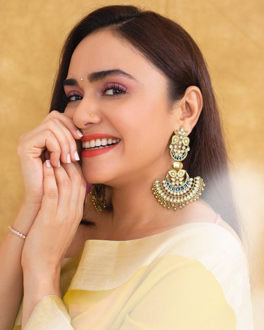 Amruta Khanvilkar in a lime yellow mint and oranges saree for an ott launch